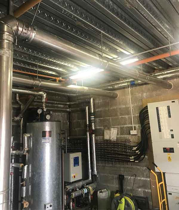 commercial gas hot water boiler system installed in a basement of a factory